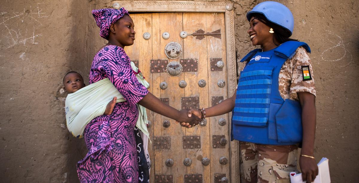 An UNPOL officer greets a woman and her baby while on patrol in Timbuktu